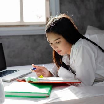 Hausaufgaben der asiatischen frau auf dem bett