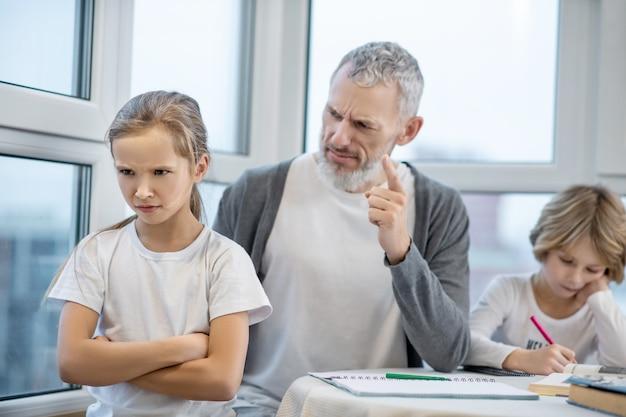 Hausaufgaben. grauhaariger bärtiger mann, der mit seinen kindern am tisch sitzt, während sie unterricht machen