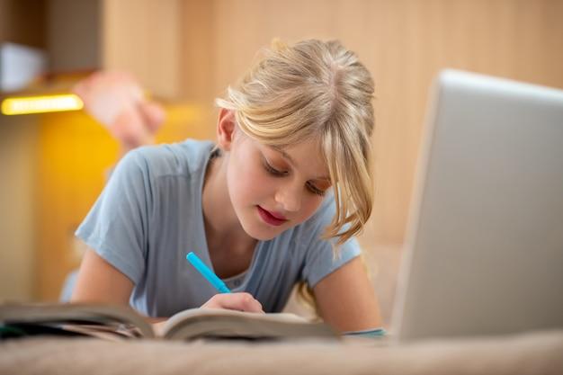 Hausaufgaben vorbereiten. ein blondes mädchen liegt auf dem bett und macht ihren unterricht