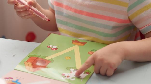 Hausaufgaben während des online-unterrichts zu hause, soziale distanzquarantäne covid-19, selbstisolation, online-bildungskonzept, homeschooling. kind zu hause, kindergarten geschlossen. kleinkindmädchen im vorschulalter.