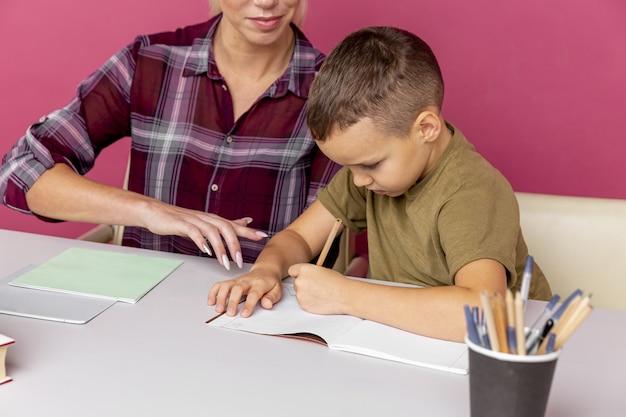 Hausaufgaben zusammen im quarantänekonzept. mutter mit kind, das mit büchern am schreibtisch sitzt und studiert.