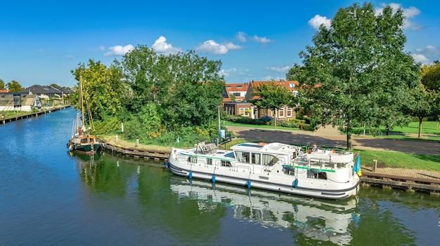 Hausbootreise im kanal im typischen niederländischen dorf auf dem land, kreuzfahrtbooturlaub in den niederlanden