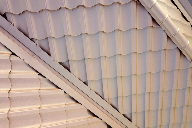 Hausdachkonstruktion mit braunen metallziegelplatten bedeckt.