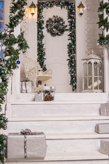 Hauseingang verziert für holidays.garland von niederlassungen und von lichtern auf dem geländer festlich verziertes haus. laterne, geschenkboxex in silber.ferienpostkarte