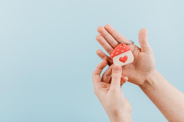 Hausfigur mit einem roten herzen in der kinderhand