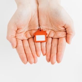 Hausform keychain in den weiblichen händen gegen weißen hintergrund