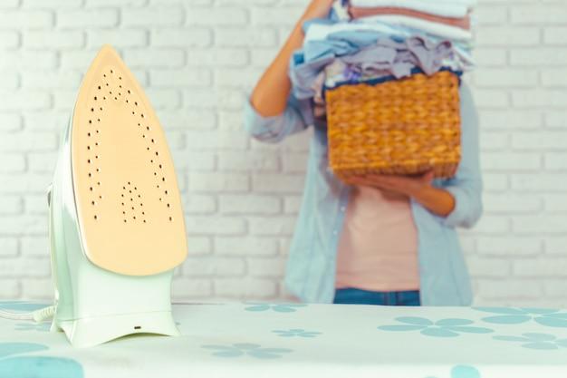 Hausfrau bringt einen riesigen haufen wäsche auf das bügelbrett