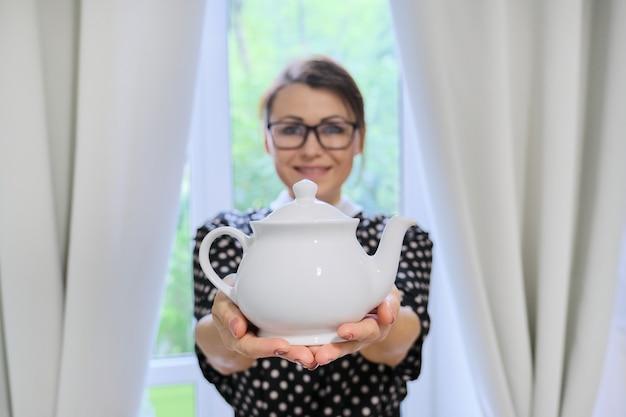 Hausfrau der erwachsenen frau mit teekanne, frau, die weiße porzellanteekanne in den händen hält, zu hause nahe fenster mit vorhängen, teezeit stehend