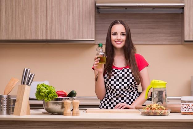 Hausfrau der jungen frau, die in der küche arbeitet