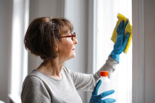 Hausfrau, die das fenster säubert
