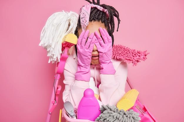 Hausfrau, die es satt hat, alle hausschreie und nachteile aufzuräumen, gesicht mit händen in gummihandschuhen, umgeben von reinigungsmitteln, drückt negative emotionen einzeln auf rosa aus