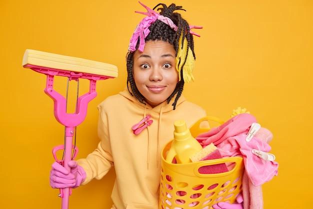 Hausfrau, die in lässigen sweatshirt-schutzhandschuhen aus gummi gekleidet ist, hält einen korb voller wäsche mit reinigungsmitteln und mopp, der an der hausarbeit isoliert auf gelb beteiligt ist