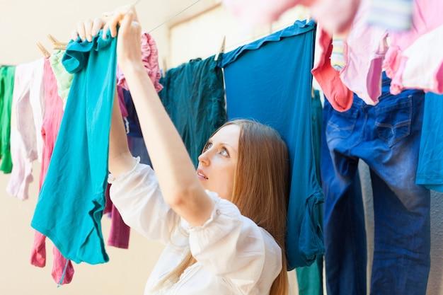Hausfrau, die kleidung auf wäscheleine trocknet