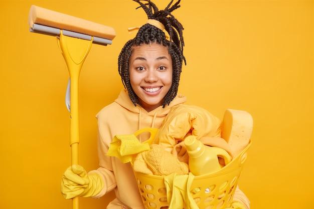 Hausfrau, die mit hausarbeit beschäftigt ist, reinigt das haus, bevor der urlaub mop hält und einen wäschekorb trägt, der gut gelaunt ist, isoliert auf gelb