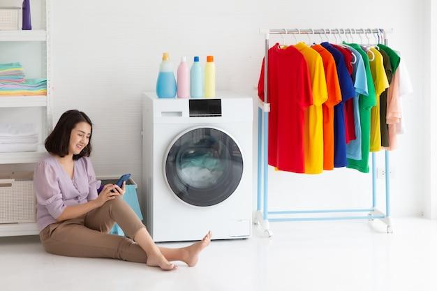 Hausfrau, die mit stoffwaschmaschine auf dem boden sitzt und smartphone während der hausarbeit beobachtet,