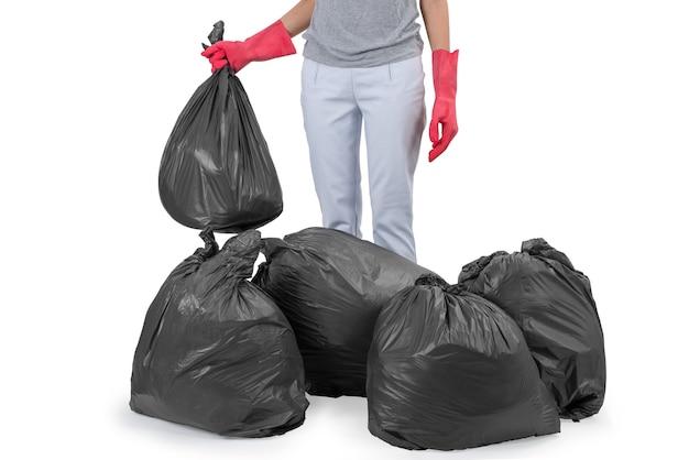 Hausfrau, die unter den abfallbeuteln getrennt auf weiß steht