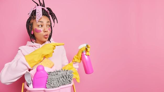 Hausfrau hält sprühwaschmittel bereit für den reinigungsservice zeigt beiseite auf kopienraum gibt ideen oder tipps trägt gummihandschuhe freizeitkleidung isoliert auf rosa