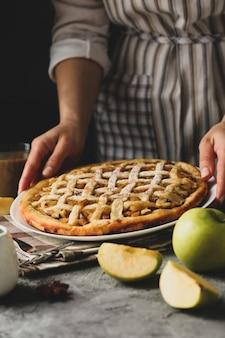 Hausfrau halten leckeren apfelkuchen auf grauem tisch. hausgemachtes essen