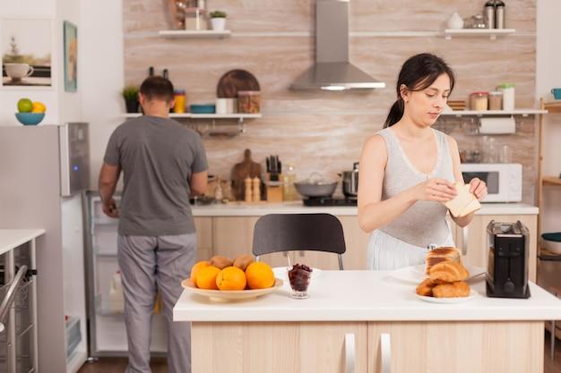 Hausfrau im pyjama bereitet das frühstück vor und macht geröstetes brot auf elektrischem toaster. junges paar am morgen, das essen zusammen mit zuneigung und liebe zubereitet