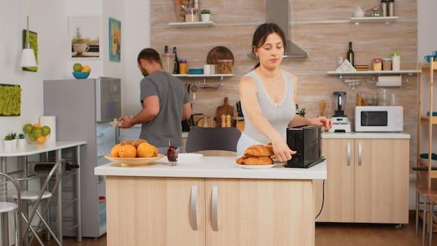 Hausfrau im pyjama bereitet das frühstück vor und macht geröstetes brot auf elektrischem toaster. junges paar am morgen, das zusammen mit zuneigung und liebe das essen zubereitet