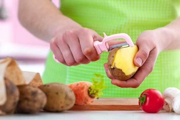 Hausfrau im schutzblech, das reifer kartoffel mit einem schäler für frischgemüseteller zu hause kocht.