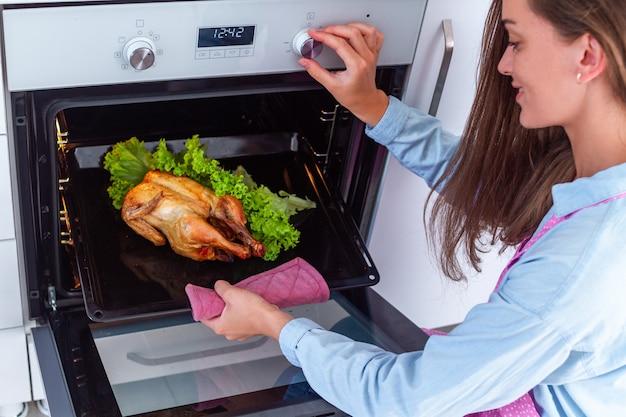 Hausfrau in der schürze, die ganzes gegrilltes huhn mit gemüse im ofen zum abendessen backt. zu hause kochen