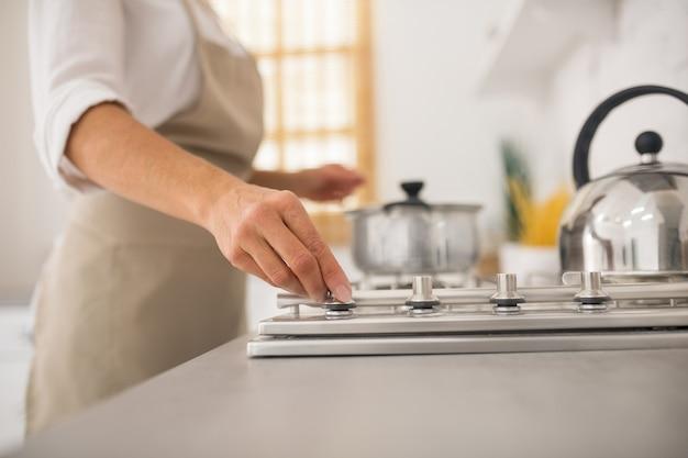 Hausfrau in der schürze, die in der küche kocht