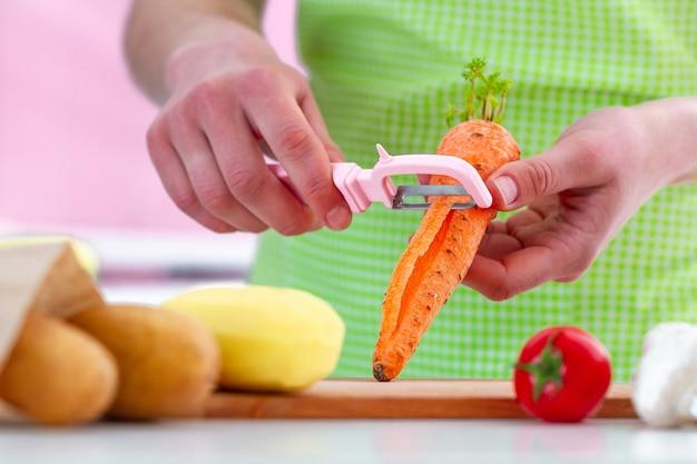 Hausfrau in der schürze, die reifer karotte mit einem schäler für das kochen von frischgemüsegerichten und -salaten abzieht.
