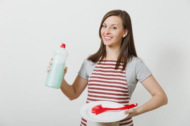 Hausfrau in gestreifter schürze isoliert. haushälterin hält flaschenreinigerflüssigkeit, rote bürste zum abwaschen, weiße leere runde platte