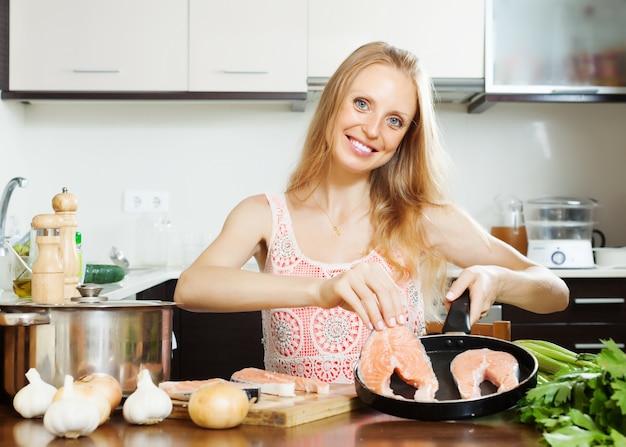 Hausfrau kocht lachs in der küche
