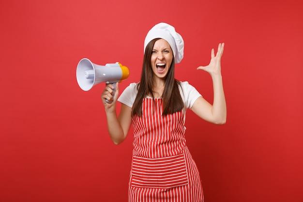 Hausfrau köchin oder bäckerin in gestreifter schürze t-shirt haube kochmütze isoliert auf rotem wandhintergrund. schockierte frau schreit im megaphon, kündigt rabattverkauf an. mock-up-kopierraumkonzept.