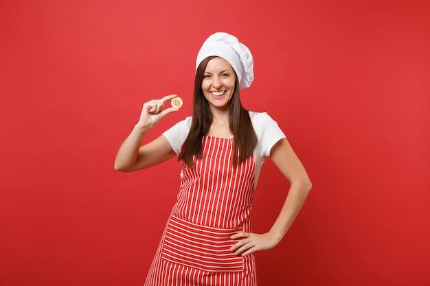 Hausfrau köchin oder bäckerin in gestreifter schürze weißes t-shirt haube kochmütze isoliert auf rotem wandhintergrund. lächelnde frau, die bitcoin hält, zukünftige währung der bitmünze. mock-up-kopierraumkonzept.