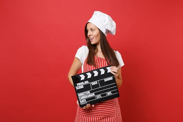 Hausfrau köchin oder bäckerin in gestreifter schürze, weißes t-shirt, haubenköche isoliert auf rotem wandhintergrund. frau, die klassischen schwarzen film hält, der filmklappe macht. mock-up-kopierraumkonzept.