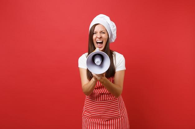 Hausfrau köchin oder bäckerin in gestreifter schürze, weißes t-shirt, haubenköche isoliert auf rotem wandhintergrund. frau schreit im megaphon, kündigt rabattverkauf an. mock-up-kopierraumkonzept.