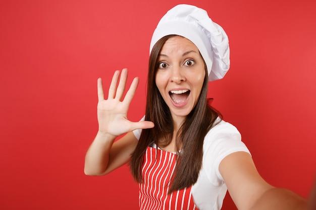Hausfrau köchin oder bäckerin in gestreifter schürze, weißes t-shirt, haubenköche isoliert auf rotem wandhintergrund. haushälterin frau hautnah dabei selfie-schuss machen. mock-up-kopierraumkonzept.