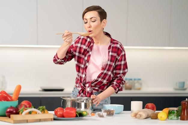 Hausfrau mit einer kurzen frisur, die ein essen probiert, während sie das mittagessen für die familie in der moderne kocht