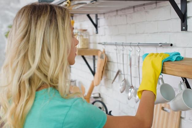 Hausfrau mit gummihandschuhen, die regal mit mikrofasertuch abwischen