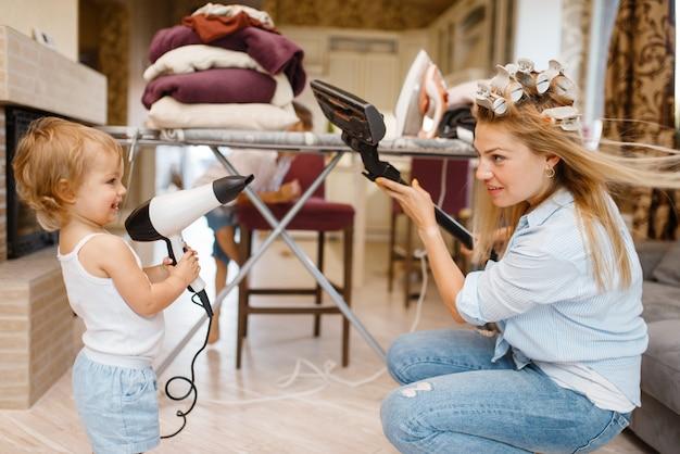 Hausfrau mit kleinem kind spielt staubsauger und fön am bügelbrett. frau mit kind, die hausarbeit zu hause zusammen macht. weibliche person mit tochter, die spaß in ihrem haus hat