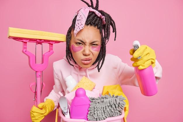 Hausfrau posiert mit hausputzwerkzeugen kümmert sich um reinheit grinsen gesicht sieht gewissenhaft auf etwas schmutziges hält mop reinigungsmittel isoliert auf rosa