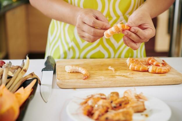 Hausfrau schält gekochte garnelen