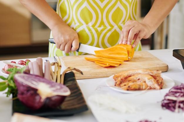 Hausfrau schneidet süßkartoffel