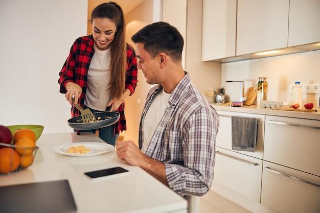 Hausfrau serviert ihrem männlichen ehepartner frühstück