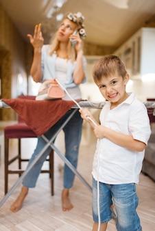 Hausfrau telefoniert, kind albert mit eisen in der küche. frau mit kind, das zusammen zu hause spielt weibliche person mit ihrem verspielten sohn in ihrem haus