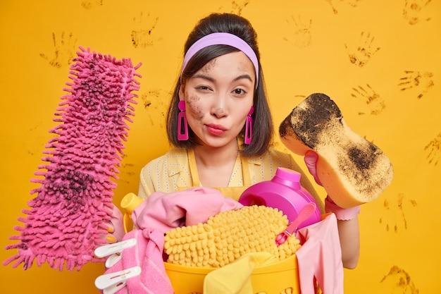 Hausfrau trägt stirnband rosa ohrringe hält schmutzigen schwamm und mopp versorgt sie mit reinigungsservice trägt wäschekorb mit wirksamen reinigungsmitteln