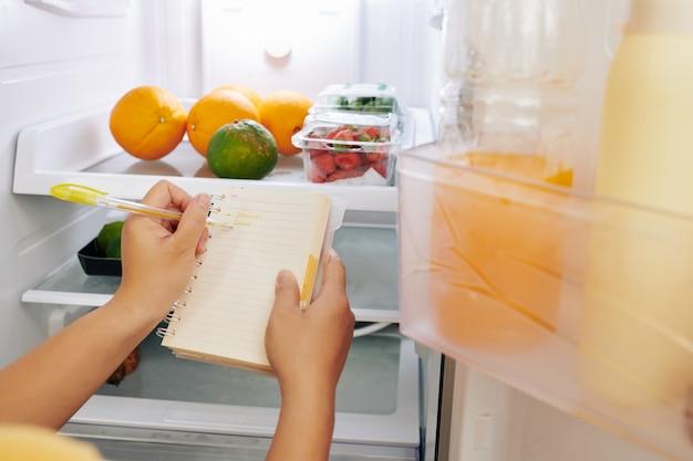 Hausfrau überprüft kühlschrank