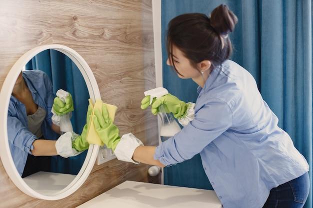 Hausfrau wacht zu hause auf. dame in einem blauen hemd. frau sauberen spiegel.