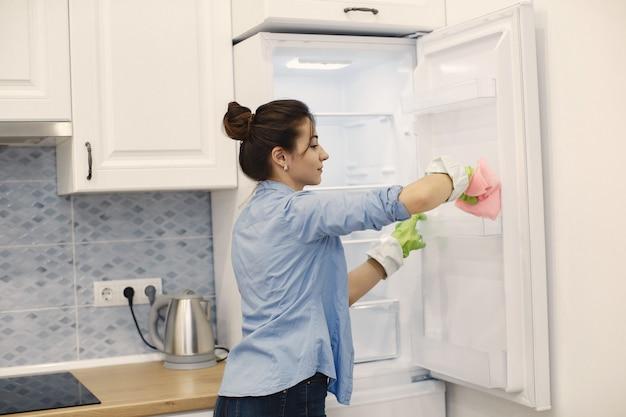 Hausfrau wacht zu hause auf. dame in einem blauen hemd.
