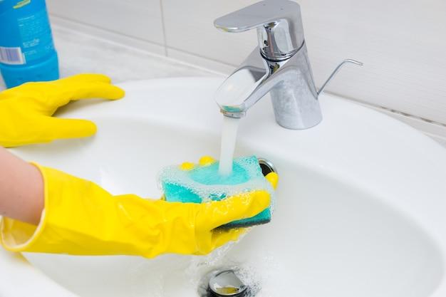 Hausfrau wäscht das handwaschbecken im badezimmer mit ihren behandschuhten händen und spült einen schwamm unter dem fließenden wasser aus dem wasserhahn oder wasserhahn ab, nahaufnahme an ihren händen