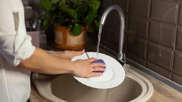 Hausfrau wäscht geschirr in der küchenspüle