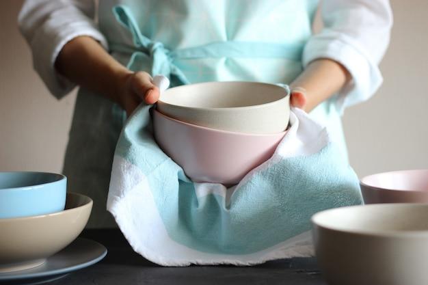 Hausfrau wischt das geschirr mit einem handtuch ab